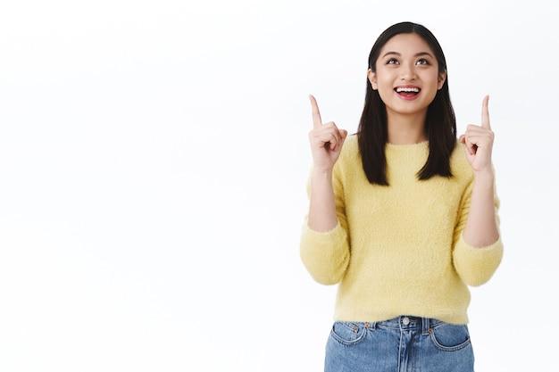 Gelukkig tevreden schattig dromerig aziatisch meisje dat iets moois ziet, precies vond wat nodig was in de winkel, wijzend en opkijkend met een verbaasde vrolijke glimlach, opgelucht of opgetogen