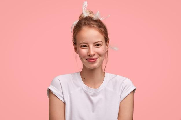Gelukkig tevreden vrouw blij om koffie te ontvangen op bed van minnaar, gekleed in een casual t-shirt, heeft veren op het hoofd
