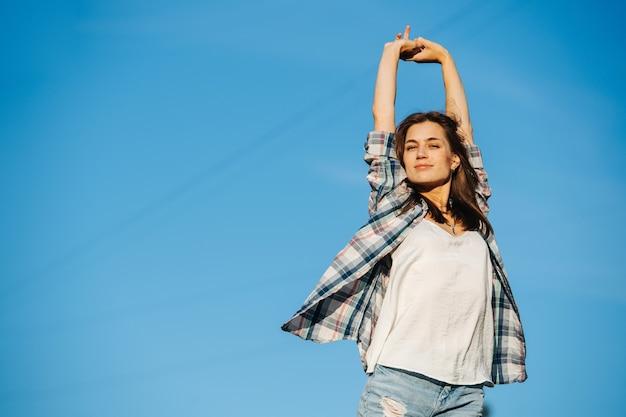 Gelukkig tevreden vrouw die zich uitstrekt genietend van de zon tegen de hemel
