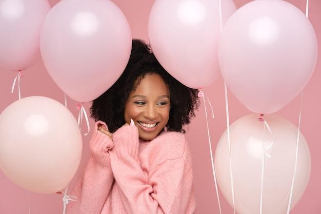Gelukkig tevreden vrouw met krullend haar met veel ballonnen