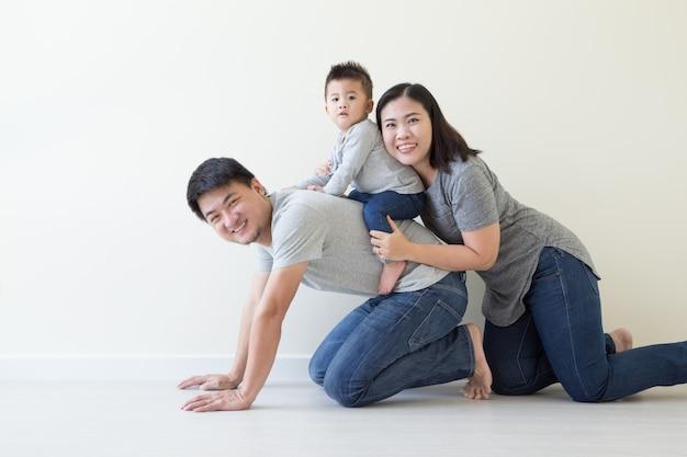 Gelukkig thaise en chinese afkomst familie met een babyjongen samen plezier op verdieping