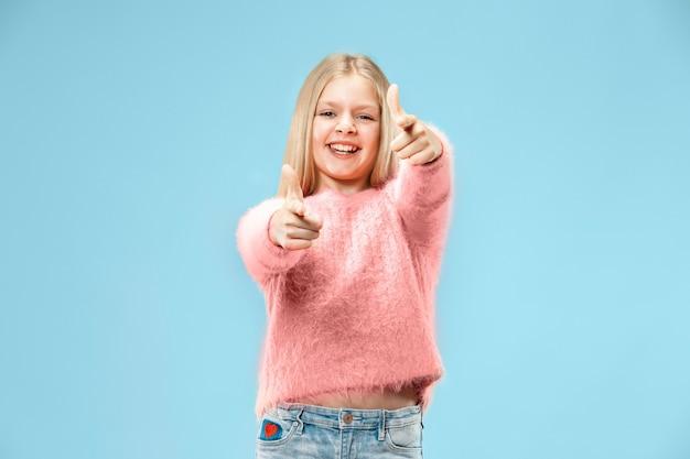 Gelukkig tiener meisje permanent, glimlachend geïsoleerd op trendy blauwe studio.