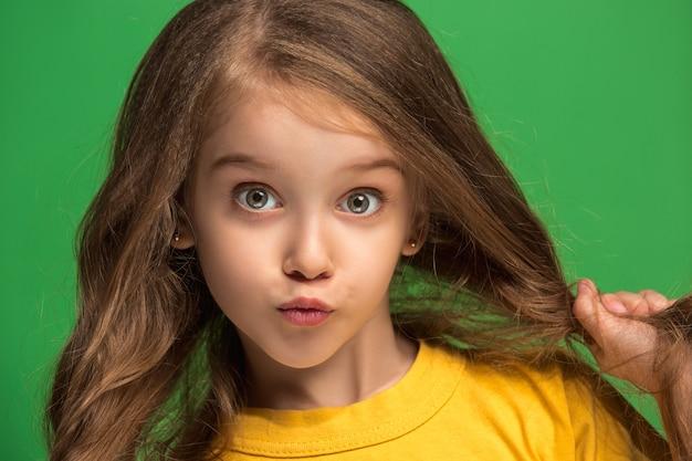 Gelukkig tiener meisje permanent, glimlachend geïsoleerd op trendy groene studio achtergrond.