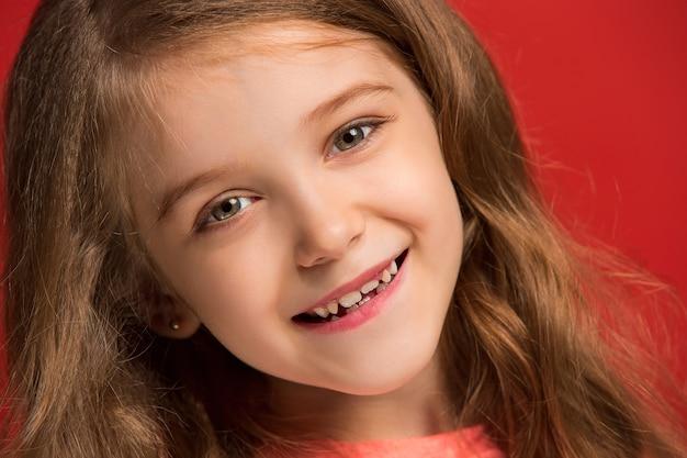 Gelukkig tiener meisje permanent, glimlachend geïsoleerd op trendy rode studio