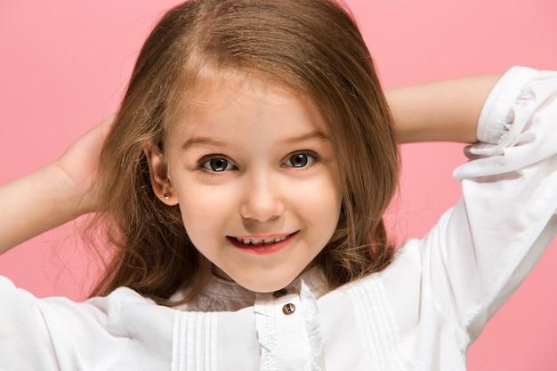 Gelukkig tiener meisje permanent, glimlachend geïsoleerd op trendy roze studio achtergrond. mooi vrouwelijk portret. jong stel tevreden meisje