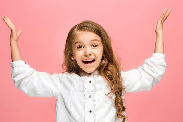 Gelukkig tiener meisje permanent, glimlachend geïsoleerd op trendy roze studio achtergrond.