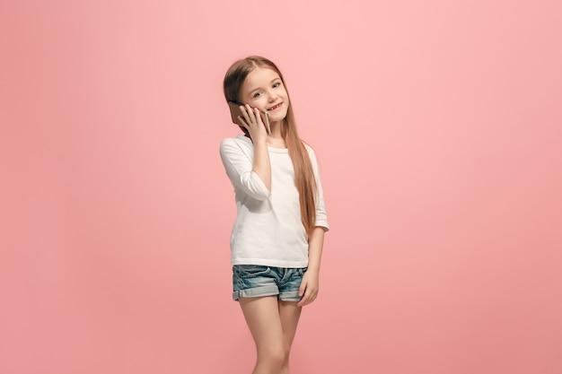 Gelukkig tiener meisje permanent, glimlachend met mobiele telefoon over trendy roze studio achtergrond. mooi vrouwelijk portret van halve lengte