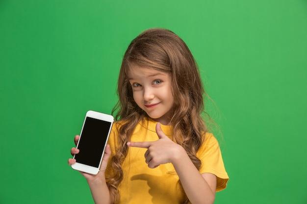 Gelukkig tiener meisje staan, glimlachend met mobiele telefoon over trendy groen. mooi vrouwelijk portret van halve lengte