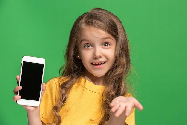 Gelukkig tiener meisje staan, glimlachend met mobiele telefoon over trendy groene studio.