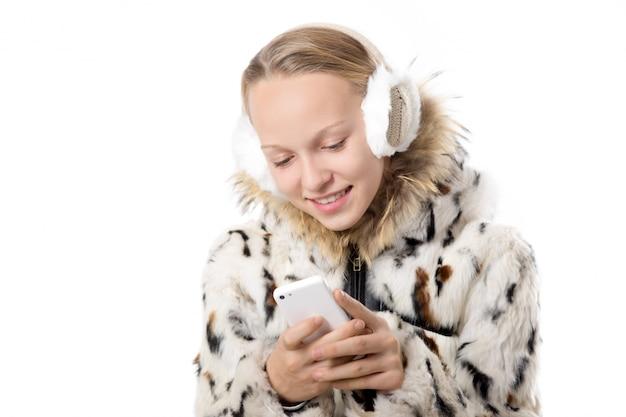 Gelukkig tiener met oorkleppen met behulp van haar mobiele telefoon