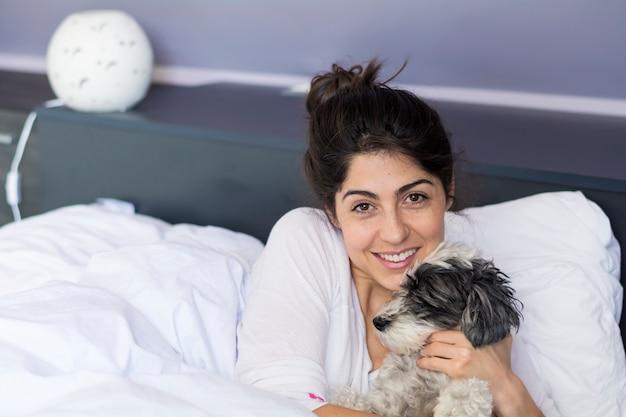 Gelukkig tiener poseren met haar hond in de slaapkamer