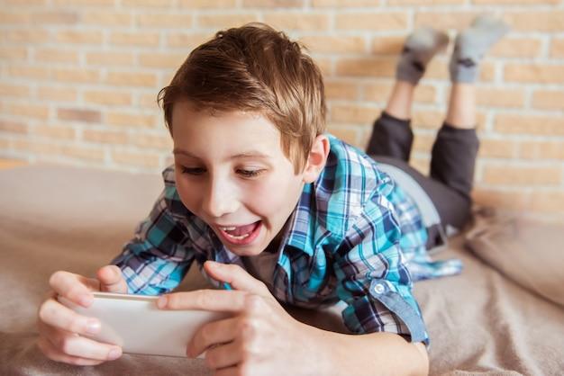 Gelukkig tiener spelen in de smartphone