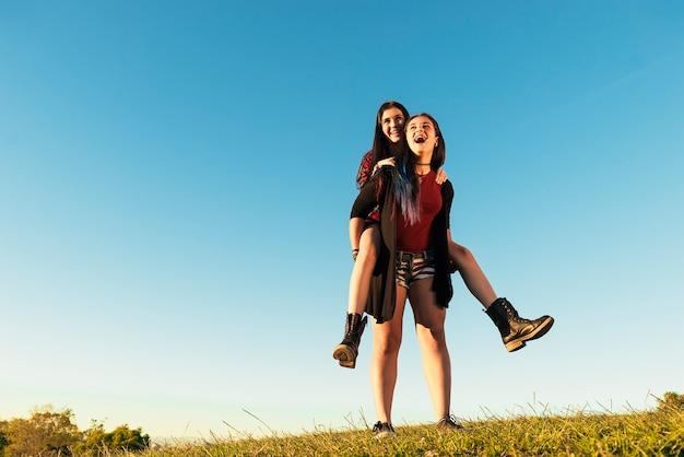 Gelukkig tienermeisje dat haar vriend meelift in het park