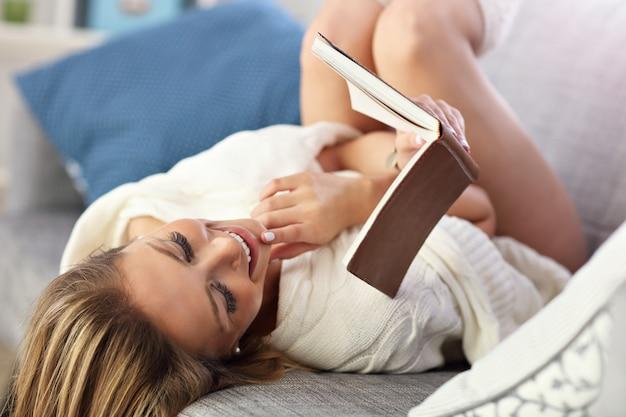 Gelukkig tienermeisje dat op de bank in de woonkamer rust terwijl ze haar favoriete romanboek leest