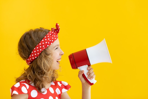 Gelukkig tienermeisje dat rode luidspreker houdt tegen gele muur