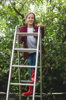 Gelukkig tienermeisje die zich voordeed op trapladder bij appeltuin