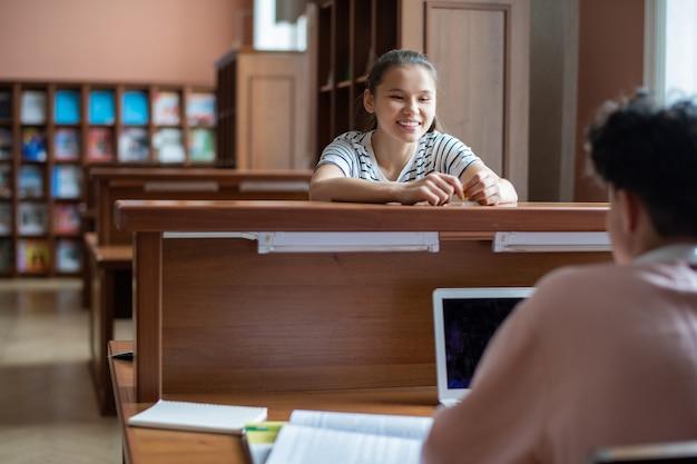 Gelukkig tienermeisje haar klasgenoot kijken met laptop tijdens gesprek in universiteitsbibliotheek na lessen