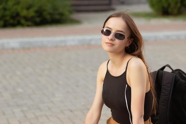Gelukkig tienermeisje in de zomer in het park zittend op een bankje