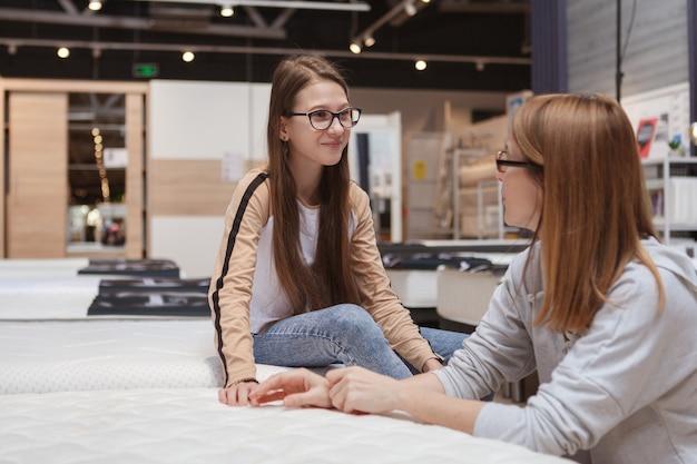 Gelukkig tienermeisje in gesprek met haar moeder tijdens het kiezen van een nieuwe orthopedische matras om te kopen