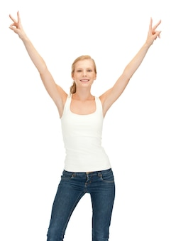 Gelukkig tienermeisje in leeg wit t-shirt met overwinningsteken