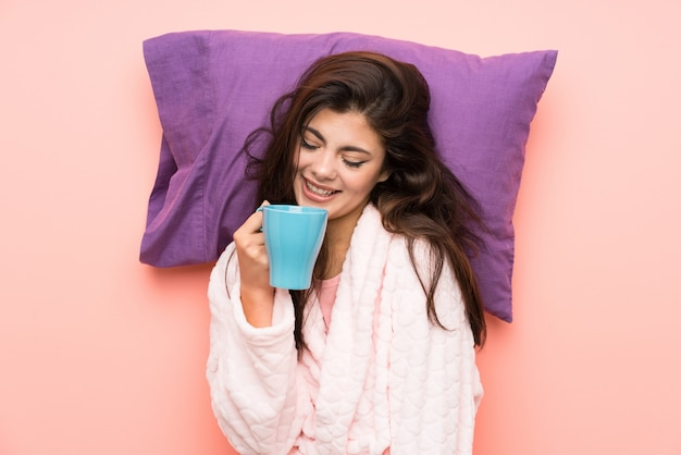Gelukkig tienermeisje in peignoir over roze backgrounnd en holding een kop van koffie