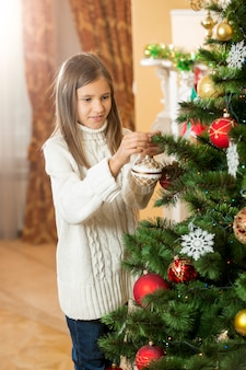 Gelukkig tienermeisje in wollen trui kerstboom versieren in huis