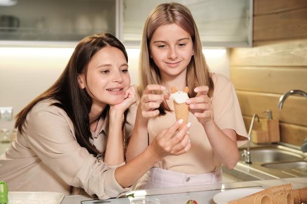 Gelukkig tienermeisje kijken naar lekker zelfgemaakt ijs in wafelkegel terwijl ze gemalen noten op de top zet met haar moeder in de buurt