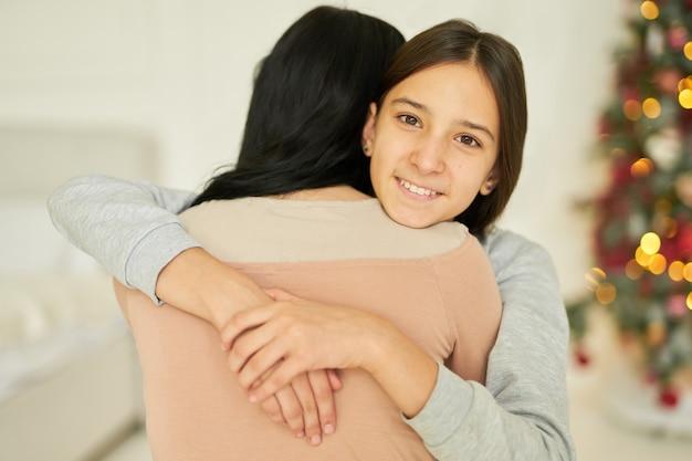 Gelukkig tienermeisje knuffelt haar moeder glimlachend in de camera terwijl ze thuis poseert, versierd voor