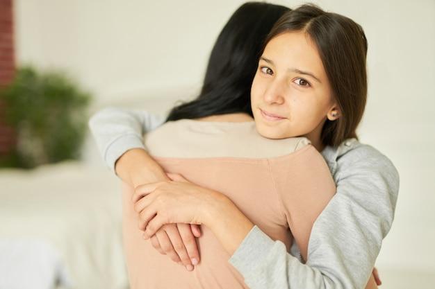 Gelukkig tienermeisje knuffelt haar moeder terwijl ze naar de camera kijkt terwijl ze thuis samen poseert