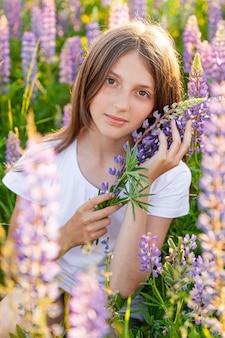 Gelukkig tienermeisje lachend buiten, rustend op de zomer veld met bloeiende wilde bloemen groen