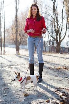 Gelukkig tienermeisje lopen met toy terriër hond met riem en boog buitenshuis