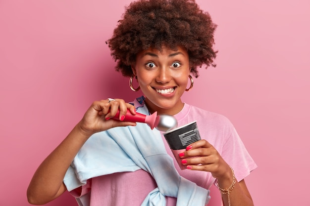 Gelukkig tienermeisje met afro haar, bijt lippen en eet smakelijk aardbeienijs, ziet er positief uit, geniet van koud zomerdessert, nonchalant gekleed, geïsoleerd over roze muur