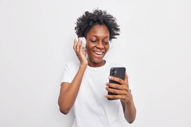Gelukkig tienermeisje met afro-kapsel kiest nummer uit afspeellijst met mobiele telefoon