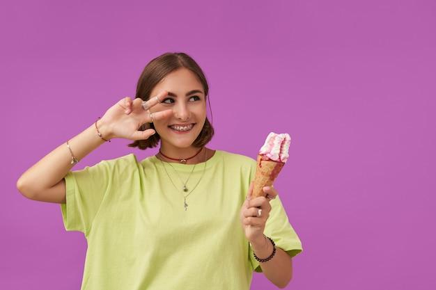 Gelukkig tienermeisje met donkerbruin haar. dame met ijs die een signaal toont, kijkt naar rechts naar de kopieerruimte boven de paarse muur. het dragen van een groen t-shirt, armbanden, ringen en kettingen