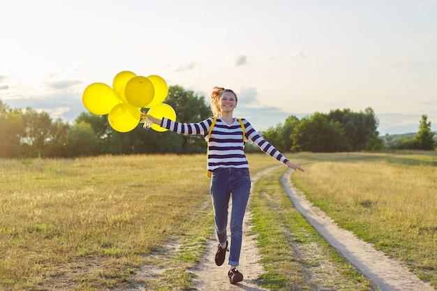 Gelukkig tienermeisje met gele ballonnen en rugzak rennen en springen langs de landweg in de zomerweide. vrijheid, leven, vreugde, vakantieconcept