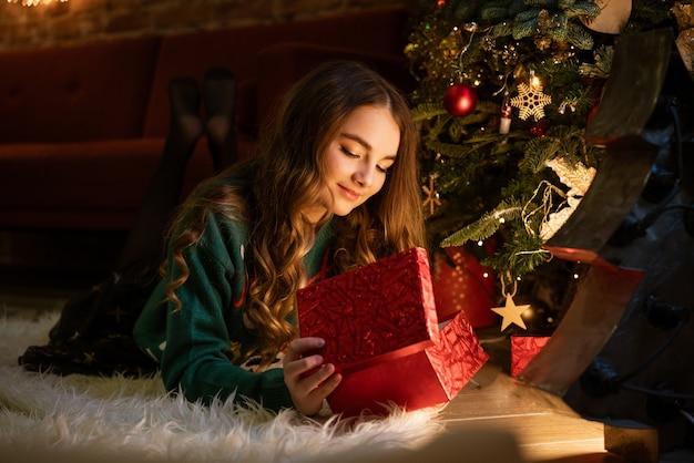 Gelukkig tienermeisje opent rode geschenkdoos zittend onder de kerstboom om middernacht in het licht van kerstmis...