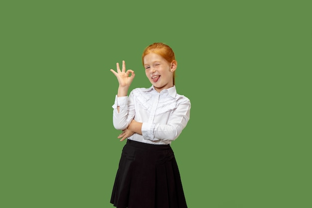 Gelukkig tienermeisje permanent, glimlachend en wijzend naar zichzelf geïsoleerd op trendy groene studio achtergrond. mooi vrouwelijk portret van halve lengte. menselijke emoties, gezichtsuitdrukking concept.