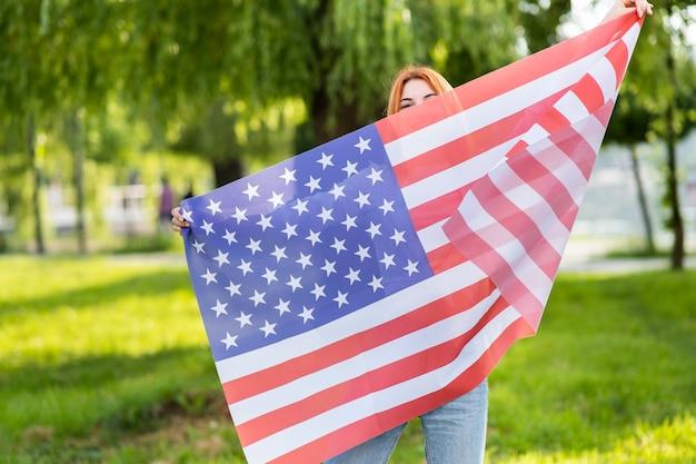 Gelukkig tienermeisje poseren met de nationale vlag van de vs die buiten in het zomerpark staat.