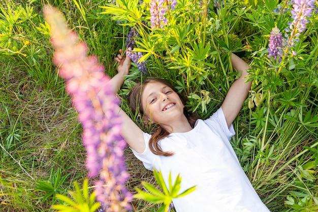 Gelukkig tienermeisje rusten liggend op zomer veld met bloeiende wilde bloemen