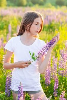 Gelukkig tienermeisje rusten op zomer veld met bloeiende wilde bloemen
