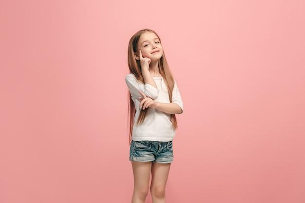 Gelukkig tienermeisje staan, glimlachend geïsoleerd op trendy roze studio
