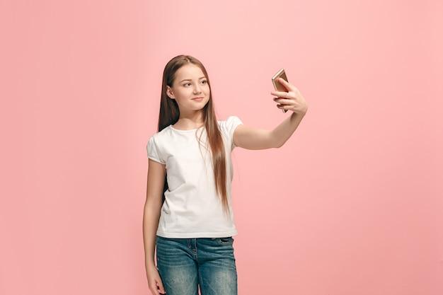 Gelukkig tienermeisje staan, glimlachend op roze studio