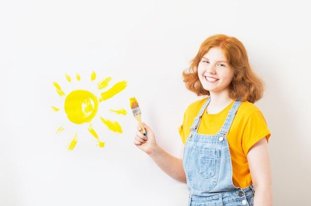 Gelukkig tienermeisje tekent zon
