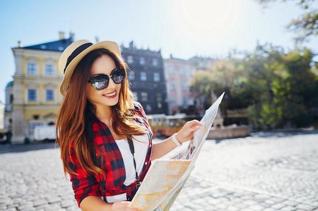 Gelukkig toeristenmeisje met bruin haar dat hoed, zonnebril en rood overhemd draagt, kaart bij oude europese stadsachtergrond houdt en glimlacht, reist.