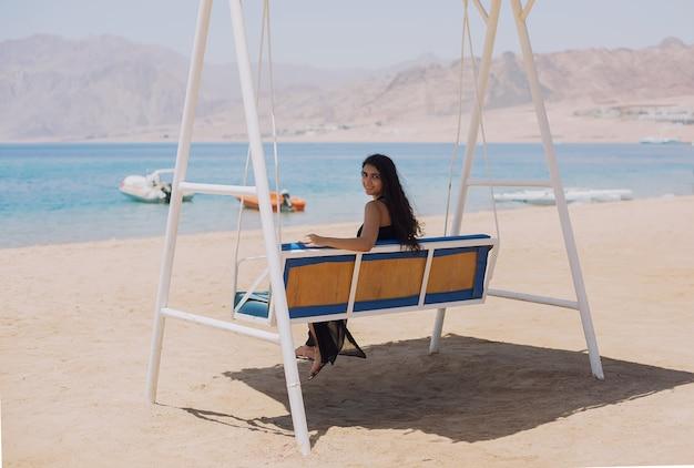 Gelukkig toeristenmeisje zit op een schommelbank met uitzicht op de lagune van de zee