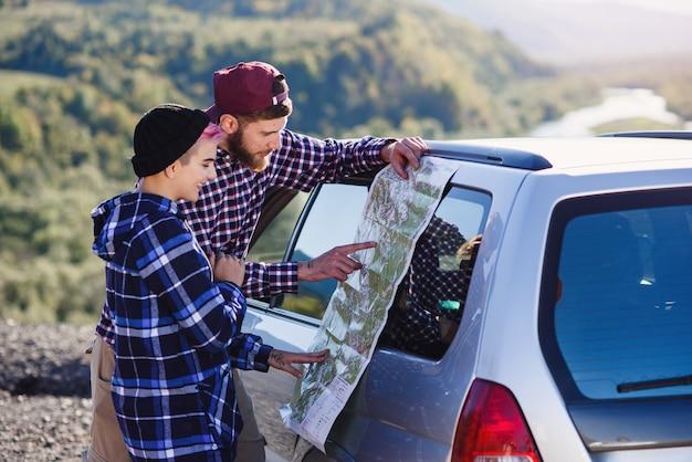 Gelukkig toeristenpaar met document kaart dichtbij auto.