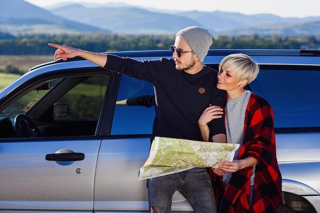 Gelukkig toeristenpaar met document kaart dichtbij gehuurde auto.