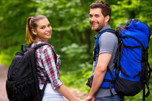 Gelukkig toeristenpaar. mooie jonge verliefde paar rugzakken dragen en over schouder kijken met een glimlach tijdens het wandelen langs het bospad