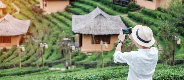 Gelukkig toeristische man in wit overhemd foto nemen door mobiele smartphone in prachtige theetuin.