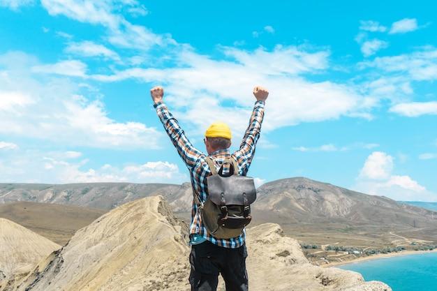 Gelukkig toeristische man met rugzak in winnaar pose op de top van de berg met uitzicht op zee